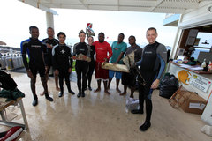 Divers display award-winning trash items picked up during the reef cleanup.