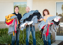 Mike McEwan, Very Jane CEO (left), JD Stice, Very Jane COO (center), and Bobbi McGraw, Safe Harbor volunteer (right), carry donated coats to the women's shelter.
