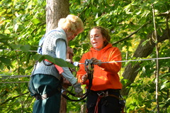 Barbara Stetson (left) is greeted at one of the treetop platforms during her climb at The Adventure Park at The Discovery Museum by park employee Ceili Grinnell. (Photo: Outdoor Ventures)