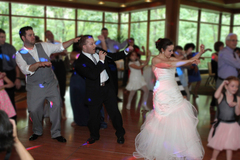 Paul on the dance floor with a bride and groom