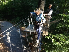 Barbara Stetson crosses a rope loops element at The Adventure Park while park president, Bahman Azarm, looks on. (Photo: Anthony Wellman, Outdoor Ventures)