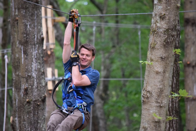 """TreeTop Adventures Owner Chris """"Topher"""" Kerr swings through the trees at Greater Boston's newest outdoor attraction."""