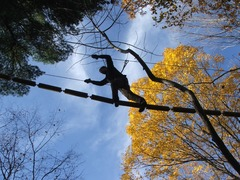 A climber at The Adventure Park seen agains the backdrop of an autumn sky and trees. (Outdoor Ventures Photo)
