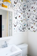 In this bathroom design, Bethany Adams uses the yellow light over the mirror and yellow trim on the shower curtain to ground the busy wallpaper featuring butterflies and birds.