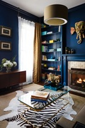 Bethany Adams isn't afraid to incorporate dark colors in her designs. In this photo, navy blue walls serve as the perfect backdrop for the colorful elephant mask in this historic home's family room.