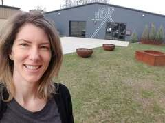 Megan Bayles Bartley, a licensed therapist in Louisville, KY, standing outside the new 1619 Flux: Art + Activism building in the city's Portland neighborhood.