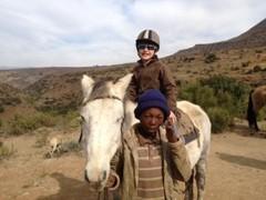 Kent Redding's son, Tate (7), enjoys pony trekking in Lesotho, Africa, on a summer family safari © Africa Adventure Consultants