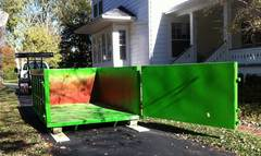 Moon's residential size dumpsters are driveway safe and placed on boards during delivery for surface protection.