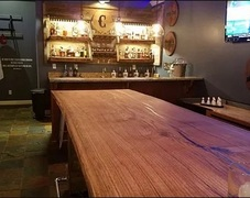 This live edge wooden table was custom built from White Oak by River City Wood Design for Troll Pub, a local bar in Louisville, Kentucky.
