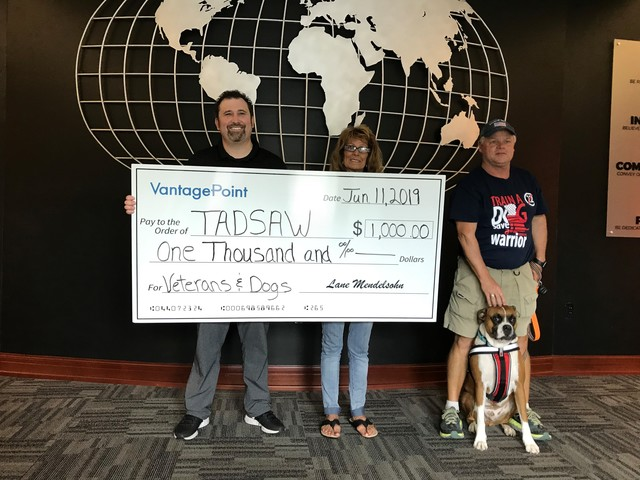 Lane Mendelsohn, president of Vantagepoint AI, presents a donation to Lynn Colombo, Cory Ball, and Nick of TADSAW