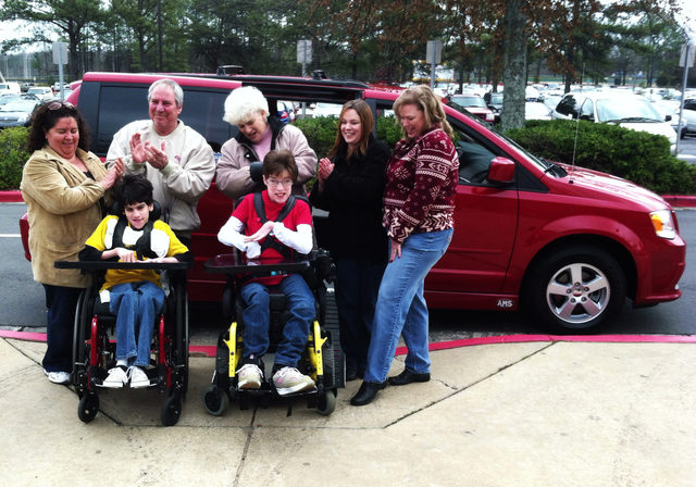 Jessica Wilson and Donnie Gooding are surrounded by family in front of the handicap van that will take them to the prom together.