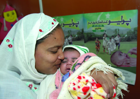 A mother in Pakistan who lost a child to pneumonia embraces her newborn. Baby Asia was just vaccinated against life-threatening Hib pneumonia. (Khalid Raja)