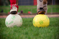Pass It Forward soccer balls come in sizes 4 (yellow) and size 5 (white).