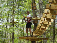"""A climber figures out how to navigate one of the bridges or """"elements"""" at The Adventure Park at Storrs. (photo by Anthony Wellman)"""