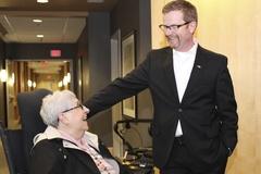 Terry Lake greets Lee Reichert, a tenant of Primrose Gardens