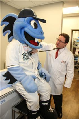Dr. Steve Heffer, the newly appointed Official General Practitioner for The Bridgeport Bluefish Baseball Team, gives B.B., the team mascot, a full check-up.