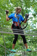 "The Adventure Park is more than just zip lines. Here a climber  navigates one of the many ""crossings"" between tree platforms. (photo: Outdoor Ventures)"