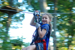 """""""Are we having fun yet?---YES!"""" A young climber enjoys one of the zip lines at The Adventure Park. (photo: Outdoor Ventures)"""