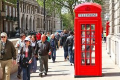 People walk past telephone booth on May 13, 2012 in London.