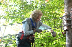 """Barbara Stetson holding tightly and navigating along the cables of one of the """"aerial trails"""" at The Adventure Park at The Discovery Museum. At age 94 she is the park's oldest climber to date."""