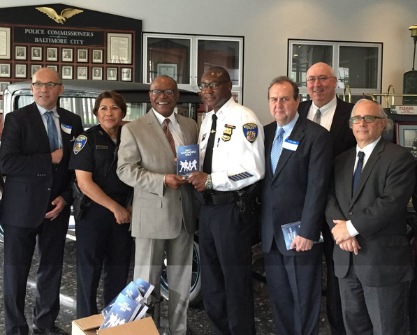 Reverend Al Hathaway (left) presents a First Responder Bible to the Baltimore Police Department along with Joey Hudson (right).
