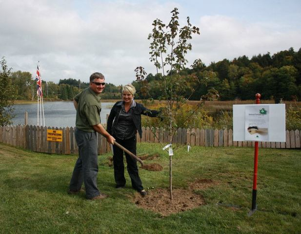 Dave Bishop, General Manager of the Haliburton Forest & Wildlife Reserve performs the ceremonial planting of a Canadian Maple with the help of Caroline Collins, Chair of PNP's Green Team.