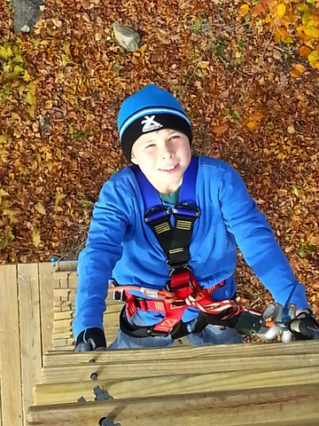 Climbing up to autumn adventure in the treetops. This young climber knows how to appreciate the fall foliage--by climbing  and zip lining through it. (Photo: Outdoor Ventures)