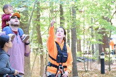 An Adventure Park Monitor points out the treetop action to some Park visitors during the Iron Monkey Competition. (Photo: Outdoor Ventures)
