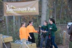 Chaya (L) and Bracha Paull are presented with their own climbing harnesses to honor their 100th climb. Park Manager Emilie McIntosh (R) presents. Colleen Dyer, Course Manager, looks on.