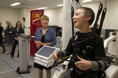 "Wesley Magee-Saxton, age 12, with Virginia Write, Senior Scientist Holland Bloorview Kids Rehabilitation Hospital says ""It feels amazing!"" as he walks using the help of the Pediatric Lokomat Pro."