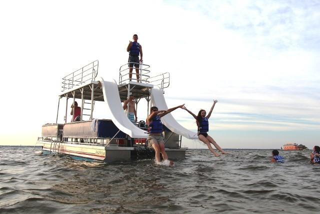 Kids watersliding off double-decker pontoon boat in Destin FL.