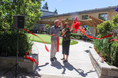 Karen Baillie (CEO) and Gerd Bartel (Board Chair) cut the ribbon - officially opening Menno Place's putting green