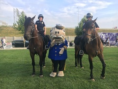 Catfish Louie, the official mascot for the Friends of the Waterfront, poses with Louisville police officers during the 2017 Fourth of July celebration in Louisville, KY.