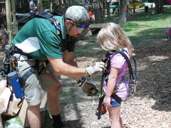 Adventure Park staffer makes sure a young climber's harness is all set.